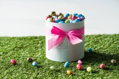 Photo for Gift box with multicolored quail Easter eggs on green grass isolated on grey - Royalty Free Image