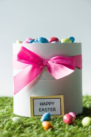 Photo for Gift box with pink bow full of colorful quail eggs isolated on grey - Royalty Free Image