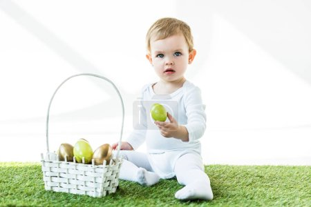 Photo for Adorable kid holding yellow chicken egg while sitting near straw basket with Easter eggs isolated on white - Royalty Free Image