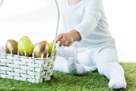 Photo for Cropped view of kid sitting near straw basket with yellow and golden chicken eggs isolated on white - Royalty Free Image