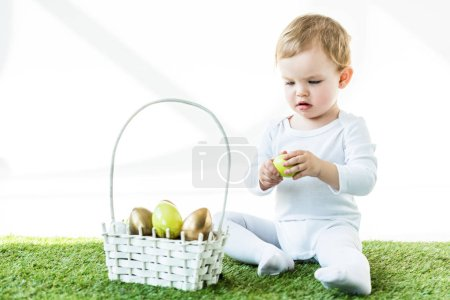 Photo for Adorable baby holding yellow chicken egg while sitting near straw basket with Easter eggs isolated on white - Royalty Free Image