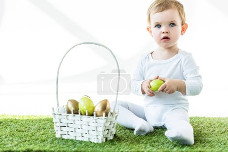 Photo for Cute blonde baby holding yellow chicken egg while sitting on green grass near straw basket with Easter eggs isolated on white - Royalty Free Image