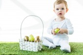 """Постер, картина, фотообои """"милый блондинка держа младенца желтое куриное яичко пока сидящ на зеленой траве около корзины сторновки с пасхальными яйцами изолированными на белом"""""""