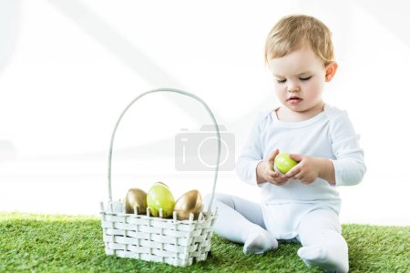 Photo for Adorable blonde child holding yellow chicken egg while sitting near straw basket with Easter eggs isolated on white - Royalty Free Image