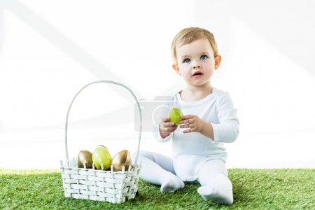 Photo for Dreamy blonde child holding yellow chicken egg while sitting on green grass near straw basket with Easter eggs isolated on white - Royalty Free Image