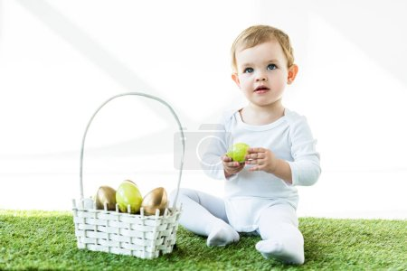 Photo for Adorable kid holding yellow chicken egg while sitting on green grass near straw basket with Easter eggs isolated on white - Royalty Free Image