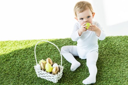 Photo for Cute child holding yellow kitchen egg near face while sitting near straw basket with Easter eggs isolated on white - Royalty Free Image