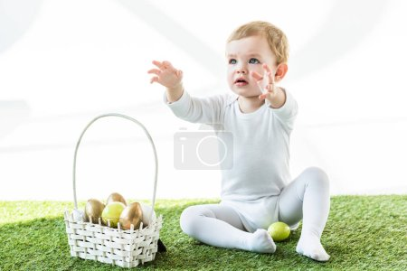 Photo for Adorable baby with outstretched hands sitting near straw basket with colorful Easter eggs isolated on white - Royalty Free Image
