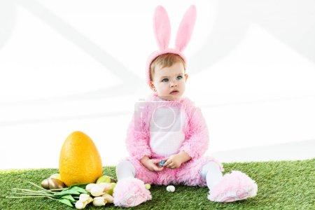 Photo pour Adorable enfant en costume de lapin drôle assis près des œufs de poulet colorés, des tulipes et des œufs d'autruche jaune isolés sur blanc - image libre de droit