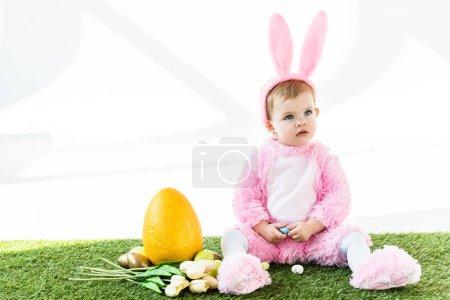 Photo pour Bébé mignon en costume de lapin drôle assis près des œufs de poulet colorés, des tulipes et de l'oeuf d'autruche jaune isolé sur blanc - image libre de droit