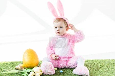 Photo pour Bébé mignon en costume de lapin drôle assis près des oeufs de Pâques, des tulipes et de l'oeuf d'autruche jaune isolé sur blanc - image libre de droit