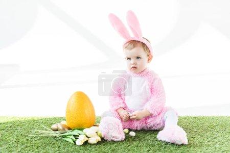 Photo pour Bébé mignon en costume de lapin drôle assis près d'oeuf d'autruche jaune, oeufs de Pâques colorés et tulipes isolées sur blanc - image libre de droit
