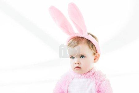Photo pour Adorable bébé coûteux dans les oreilles de lapin bandeau regardant loin isolé sur blanc - image libre de droit
