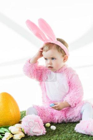 Photo pour Adorable enfant en costume de lapin drôle assis près d'oeuf d'autruche jaune, oeufs de Pâques colorés et tulipes isolées sur blanc - image libre de droit