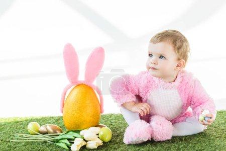 Photo pour Adorable enfant en costume rose pelucheux assis près de l'oeuf d'autruche jaune avec bandeau oreilles de lapin, oeufs de Pâques colorés et tulipes isolées sur blanc - image libre de droit