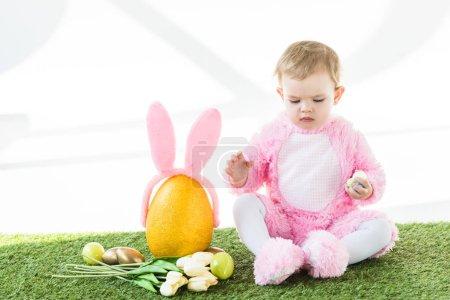 Photo pour Mignon enfant en costume rose pelucheux assis près de jaune oeuf d'autruche avec bandeau oreilles de lapin, oeufs de Pâques colorés et tulipes isolées sur blanc - image libre de droit