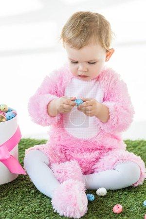 Photo pour Mignon enfant en costume rose moelleux tenant oeuf de caille bleue tout en étant assis près de la boîte avec des œufs de Pâques isolé sur blanc - image libre de droit
