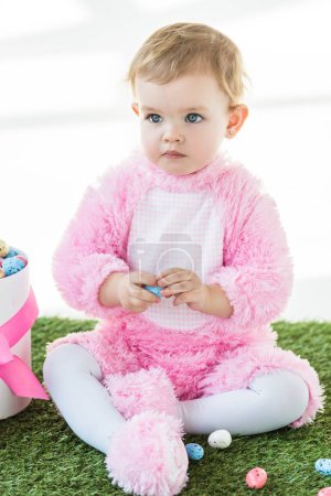 Foto de Lindo niño soñador en traje rosa esponjoso sentado cerca de la caja con huevos de Pascua aislados en blanco - Imagen libre de derechos