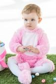 """Постер, картина, фотообои """"милый мечтательный малыш в розовом пушистом костюме сидя рядом с коробкой с пасхальными яйцами, изолированными на белом"""""""
