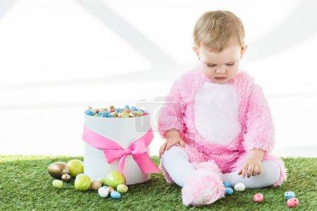 Photo pour Mignon bébé en costume rose moelleux assis près de la boîte avec des œufs de Pâques colorés isolés sur blanc - image libre de droit