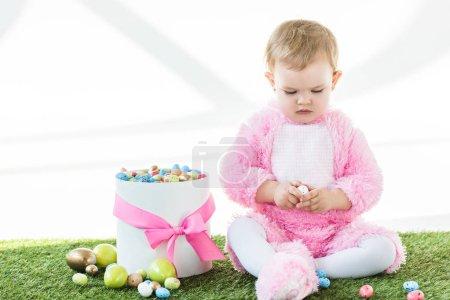 Photo pour Mignon bébé en costume rose moelleux tenant oeuf de caille tout en étant assis près de la boîte avec des œufs de Pâques colorés isolés sur blanc - image libre de droit