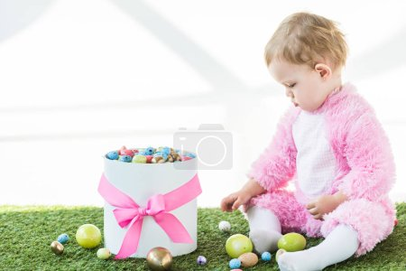 Photo for Adorable child in pink fluffy costume sitting on green grass near box with colorful Easter eggs isolated on white - Royalty Free Image
