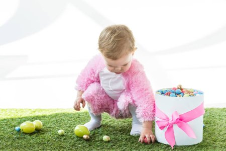Photo for Adorable kid in pink fluffy costume taking colorful eggs from green grass near gift box with pink bow isolated on white - Royalty Free Image