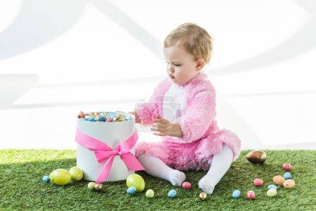 Photo pour Bébé mignon en costume moelleux rose assis sur herbe verte près de boîte-cadeau avec noeud rose et coloré oeufs de Pâques d'isolement sur fond blanc - image libre de droit