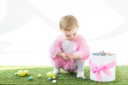 Photo for Cute baby in pink fluffy costume sitting on green grass near gift box with pink bow and colorful Easter eggs isolated on white - Royalty Free Image