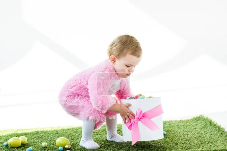 Photo for Adorable kid in pink fluffy costume holding gift box with pink bow and colorful Easter eggs isolated on white - Royalty Free Image