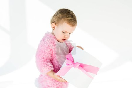Photo for Adorable child in pink fluffy costume holding gift box with pink bow isolated on white - Royalty Free Image