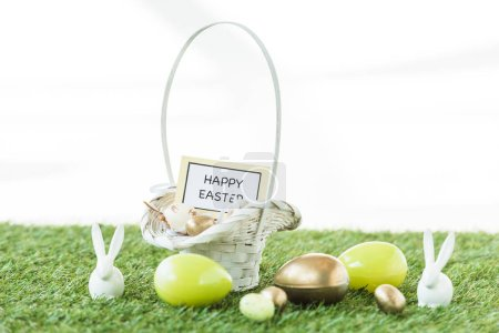 Photo for Colorful Easter eggs, decorative rabbits, and straw basket with happy Easter card on green grass isolated on white - Royalty Free Image
