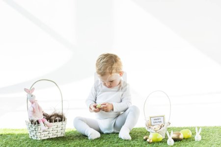 Photo for Cute kid sitting near straw baskets with Easter eggs, bunnies and happy Easter card isolated on white - Royalty Free Image