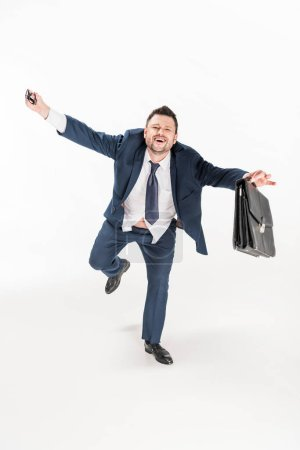 Photo for Happy overweight businessman in tight formal wear with briefcase holding glasses on white - Royalty Free Image