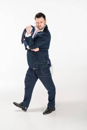 Foto de Overweight man in tight formal wear holding tie, winking and looking at camera on white - Imagen libre de derechos
