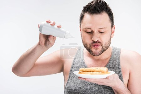 Photo for Chubby man holding bottle of syrup and waffles on white - Royalty Free Image