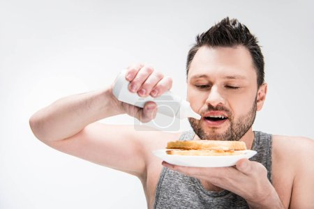 Photo for Chubby man pouring chocolate syrup on waffles isolated on white - Royalty Free Image