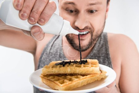 Photo for Close up view of chubby man pouring chocolate syrup on waffles isolated on white - Royalty Free Image