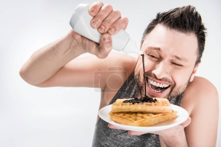 Photo for Happy chubby man pouring chocolate syrup on waffles on white - Royalty Free Image