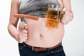 "Постер, картина, фотообои ""cropped view of overweight man showing belly and holding glass of beer with grilled sausage isolated on white"""