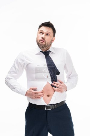 Photo for Overweight man in tight formal wear looking away while showing belly isolated on white - Royalty Free Image