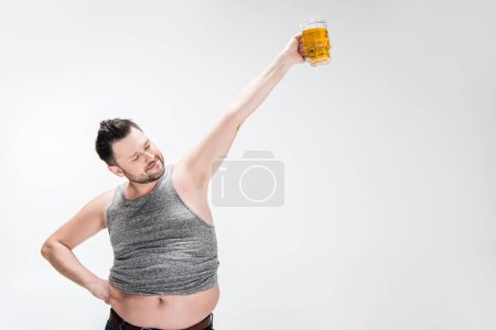 Foto de Overweight man in tank top holding glass of beer with outstretched hand on white with copy space - Imagen libre de derechos