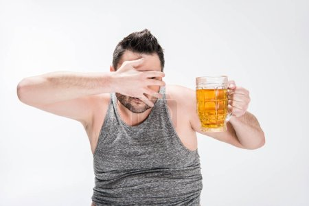 Photo for Overweight man covering face with hand and holding glass of beer on white - Royalty Free Image