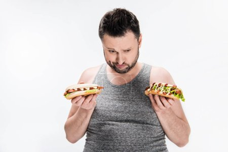 Photo for Overweight man in tank top holding hot dogs isolated on white - Royalty Free Image