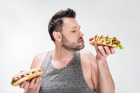 Photo for Overweight man smelling aroma of hot dog isolated on white - Royalty Free Image