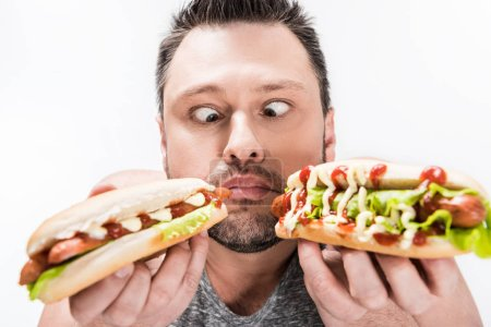 Photo pour Homme en surpoids tenant des hot-dogs et faisant expression du visage isolé sur blanc - image libre de droit