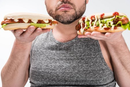 Photo for Partial view of overweight man holding hot dogs isolated on white - Royalty Free Image
