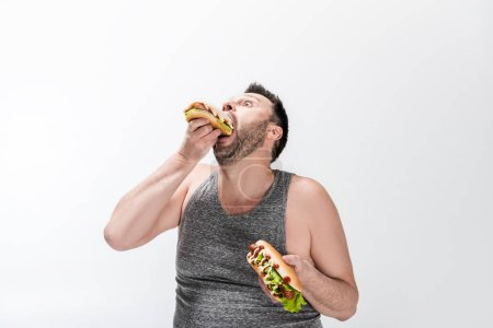 hungry overweight man in tank top eating hot dog on white