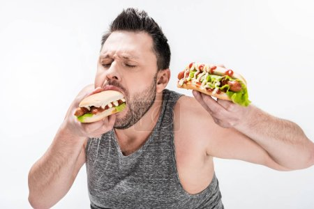 hungry overweight man in tank top eating hot dog isolated on white