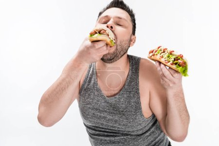 Photo for Overweight man in tank top eating tasty hot dog isolated on white - Royalty Free Image